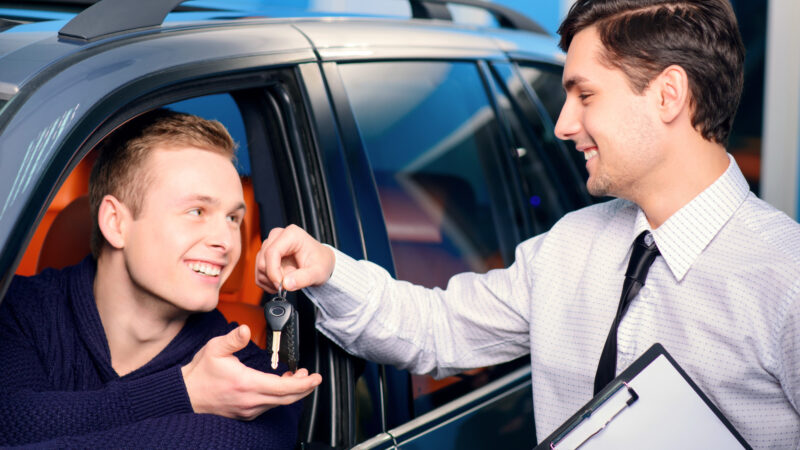 sales-manager-giving-key-from-the-new-car